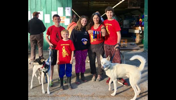 Marla Brodsky, second from right, poses with her handlers and helpers at the Annual Northern New England Sled Dog Trade Fair and Seminar in 2017. Pictured are (left to right) brothers Owen and Aidan Mahoney, Marla's daughter Ruby Rothenberg, Marla and Quinton Romer, holding Ulu. Marla and Quinton placed first and second in the four- dog rig, respectively. Marla took first in the six-dog rig, and third in the two-dog bike races. Owen and Quintong placed first and second in Cani-Cross.