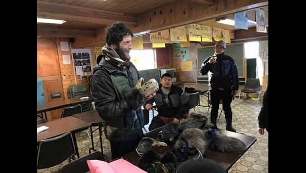 Petit tries on sealskin mittens as Ambler residents give gifts for mushers, hand sewn by former Ambler resident Myra Yupikson.